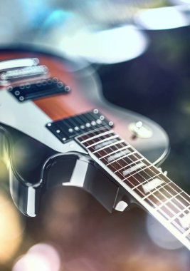 Close up shot of a guitar, over blured lights background