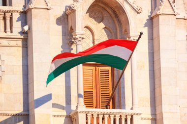 Flag of the Hungary waving in the wind on the Hungarian Parliament Building in Budapest, close-up on sunny day, Hungary