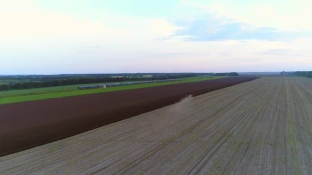 4K Aerial drone footage. Tractor plowing field. With train on background