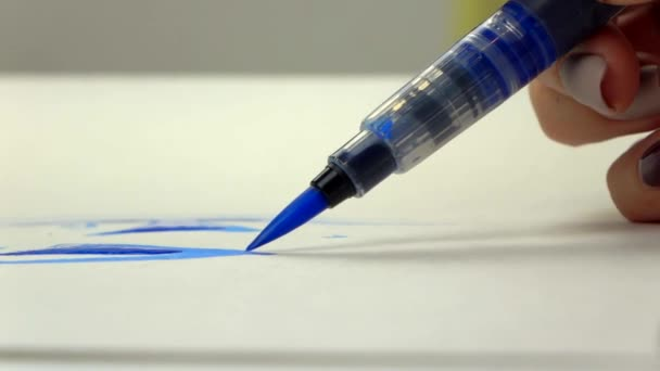 Slow-mo footage. Artist girl hand draws a watercolor brush with blue ink. close-up
