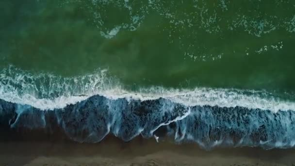 Aerial drone footage. Top view waves on beach at evening