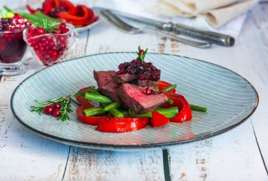 Sliced venison steak with lingonberry sauce, roast red peppers and green beans