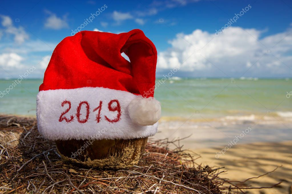 Year 2019 written at the Santa Claus hat on caribbean beach. New Year background