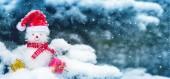 Sněhulák s vánoční dárky a sněžení. Vánoční pozadí.