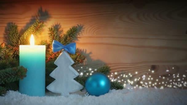 Adventskerze und blaue Dekoration mit Schnee. Weihnachtlicher Hintergrund.