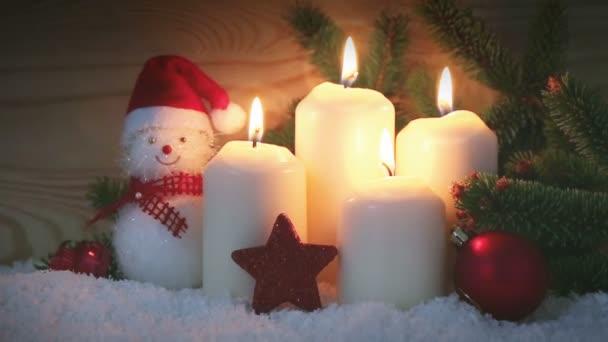vier brennende Adventskerzen und Schneemann mit rotem Weihnachtsschmuck.