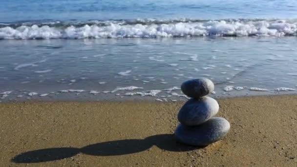 Kiegyensúlyozott szürke kövek a homokos strand.