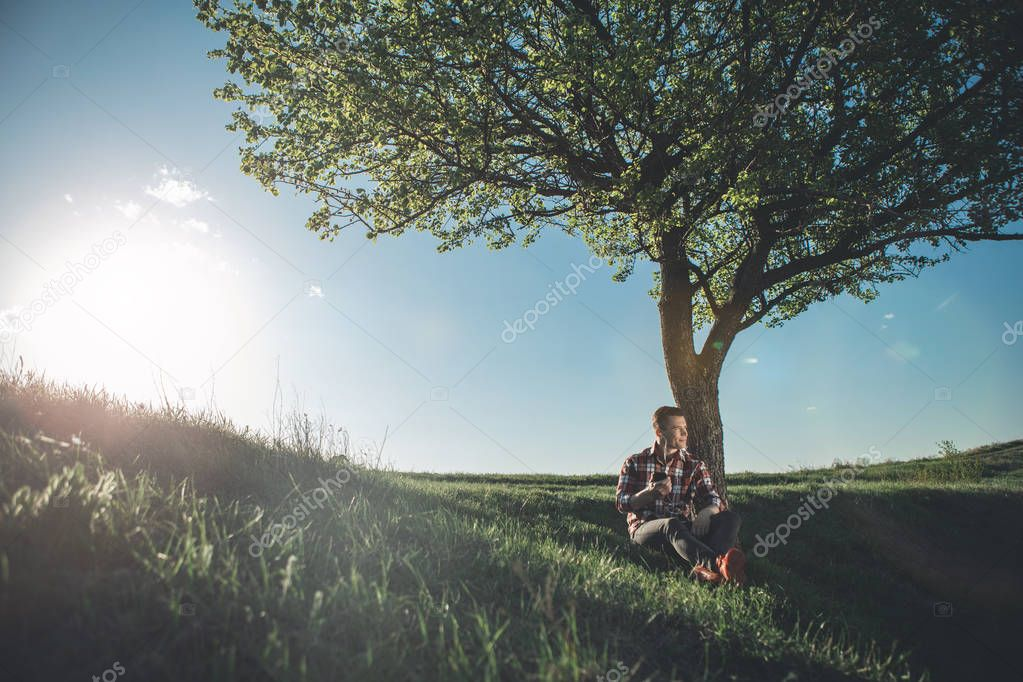 Handsome delighted man sitting nearby tree