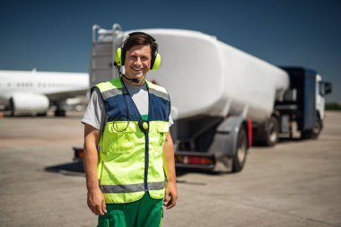 Laughing airport worker with truck on blurred background