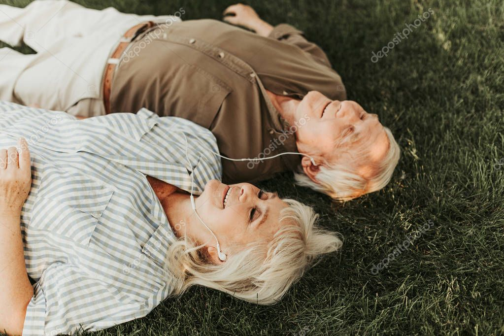 Joyous aged pair relaxing with music in earphones