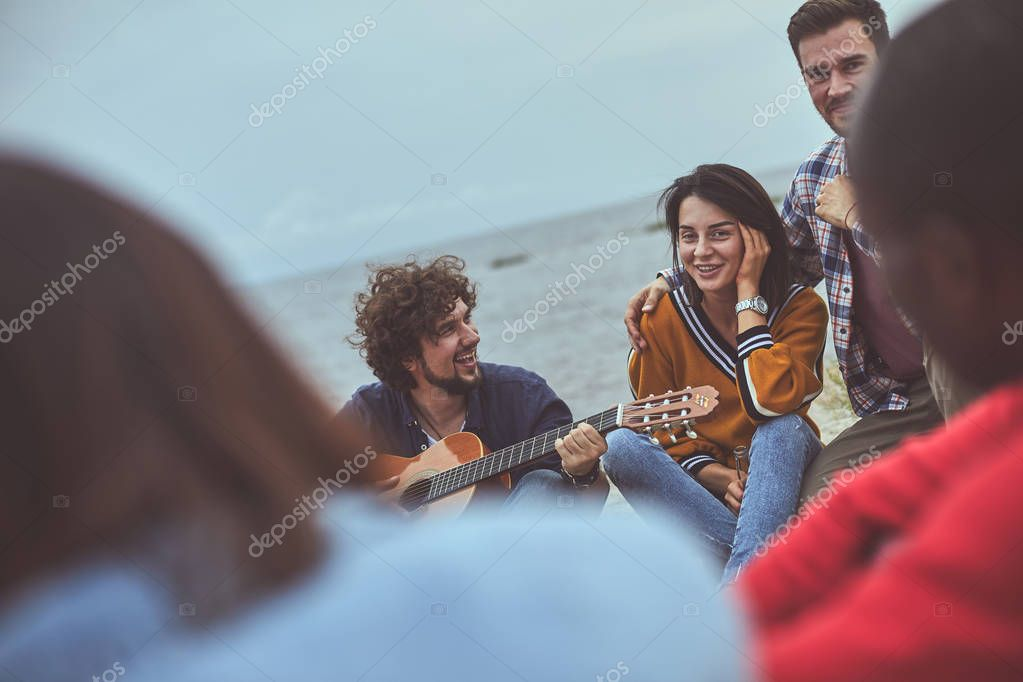 Friend playing the guitar at the seashore
