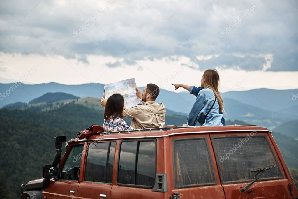 Young ambitious tourists arranging their route in the mountains