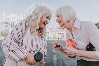 Two laughing older women are staying on square