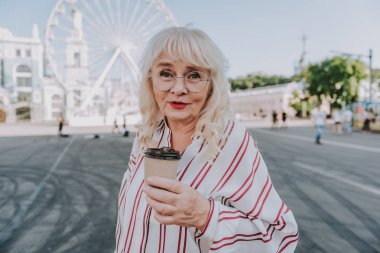 Beautiful mature woman is drinking coffee on square
