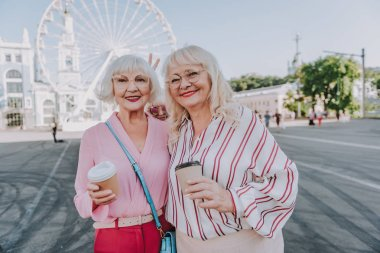 Two happy beautiful female pensioners are taking photo on square
