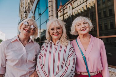 Glamorous female pensioners are taking photo on camera