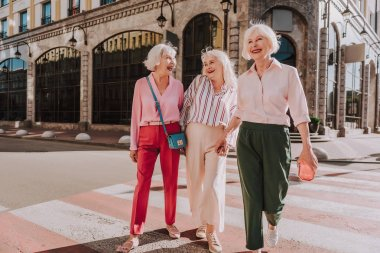 Laughing female friends in age are going across road