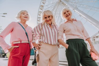 Three modern grannies are posing for photo
