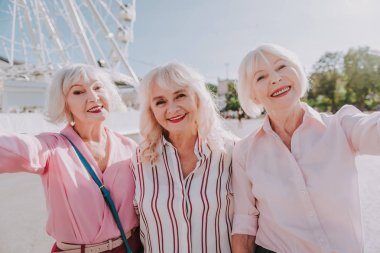 Three smiling older ladies are taking photo on camera