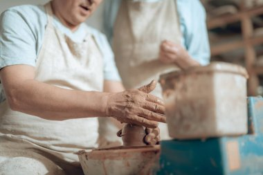 Low angle of male hands working with wet clay in potters studio