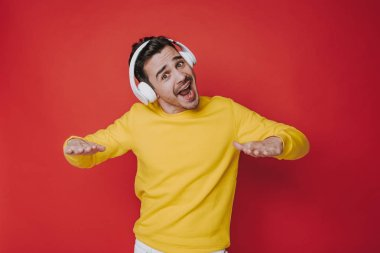 Half length of cheerful guy with headphones listening to music in studio