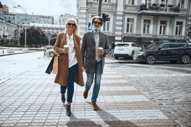 Pleased man and woman crossing the street stock photo