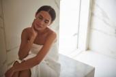 entspannte Frau schließt die Augen, während sie in einem weißen Handtuch im Hamam sitzt