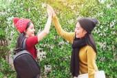 Žena student mávat a tleskat rukama se svým přítelem - přátelství a pospolitosti koncepce