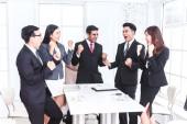 úspěšný obchodní tým slaví s rukama nahoru
