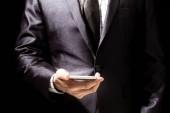Fotografie Kaufmann im eleganten schwarzen Anzug mit Smartphone auf schwarzem Hintergrund