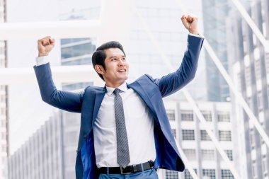 Successful businessman celebrating with arms up