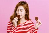 Fotografie Schöne Frau, dunkle Schokolade auf rosa Hintergrund