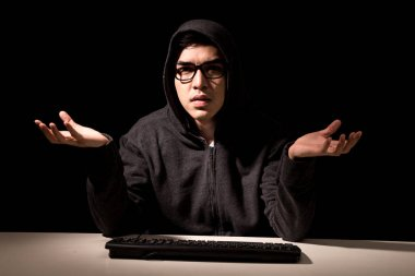 Hacker in a hood stealing information with computer on dark background