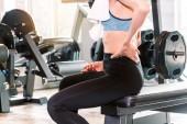 Fitness žena dotýká svaly její bolesti zad
