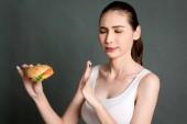Fiatal nő eszik hamburgert, szürke háttér. Szemét élelmiszer- és gyorsétterem koncepció