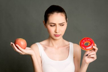 Woman holding and making choice between red apple and calorie bomb donut on gray background.Healthy eating and Junk food concept