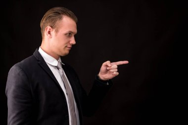 Businessman pointing to empty copy space on black background