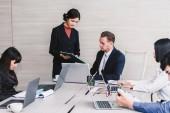 Unternehmer präsentieren und Verwendung von Laptops und diskutieren gemeinsam im Tagungsraum. Teamarbeit-Konzept