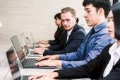 Podnikatelé používat notebooky a společně diskutovat v zasedací místnost. Koncepce týmové práce