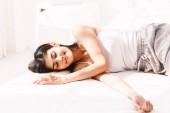 Žena spí a cítit se pohodlně na bílé posteli v ložnici