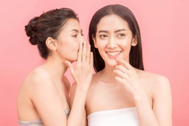 Two beautiful woman whispering gossiping on pink background