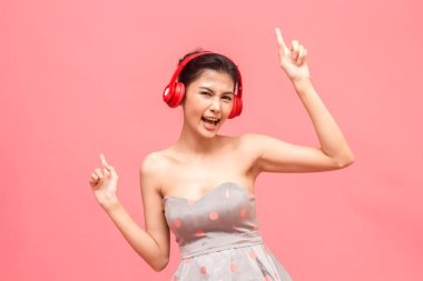 Happy woman with headphones listening to music having fun and dancing on pink background