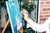 Fotografie Young woman artist drawing on canvas with color palette and watercolor paints at home