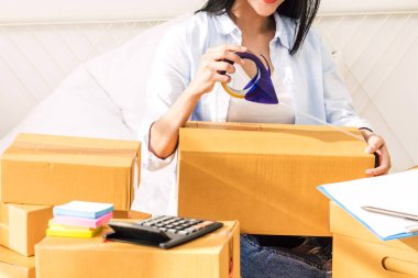 Young woman freelancer working sme business online shopping and packing cardboard box on bed at home - Business online shipping and delivery concept