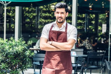 Portrait of handsome small business owner smiling and standing with crossed arms outside the cafe or coffee shop.Male barista standing at cafe