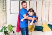 Otec s malou dcerou v kostýmu superhrdiny baví a hrát superhrdinové pohromadě doma. Láska k rodině a otec den koncepce
