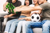 Gruppe von Freunden essen Popcorn und Bier zusammen trinken und Fußballspiel auf Sofa zu Hause beobachten. Freundschaft und Party-Konzept