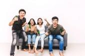 Fotografie Gruppe von Freunden, die gemeinsam Bier trinken und zu Hause auf dem Sofa ein Fußballspiel gucken.Freundschaft und Party-Konzept