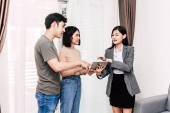 Real estate agent gazdaság tabletta, és beszélni a fiatal pár egy házban eladó. üzleti és a real estate koncepció