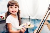 Malá holčička umělec na plátně s barevné palety a akvarel barvy doma